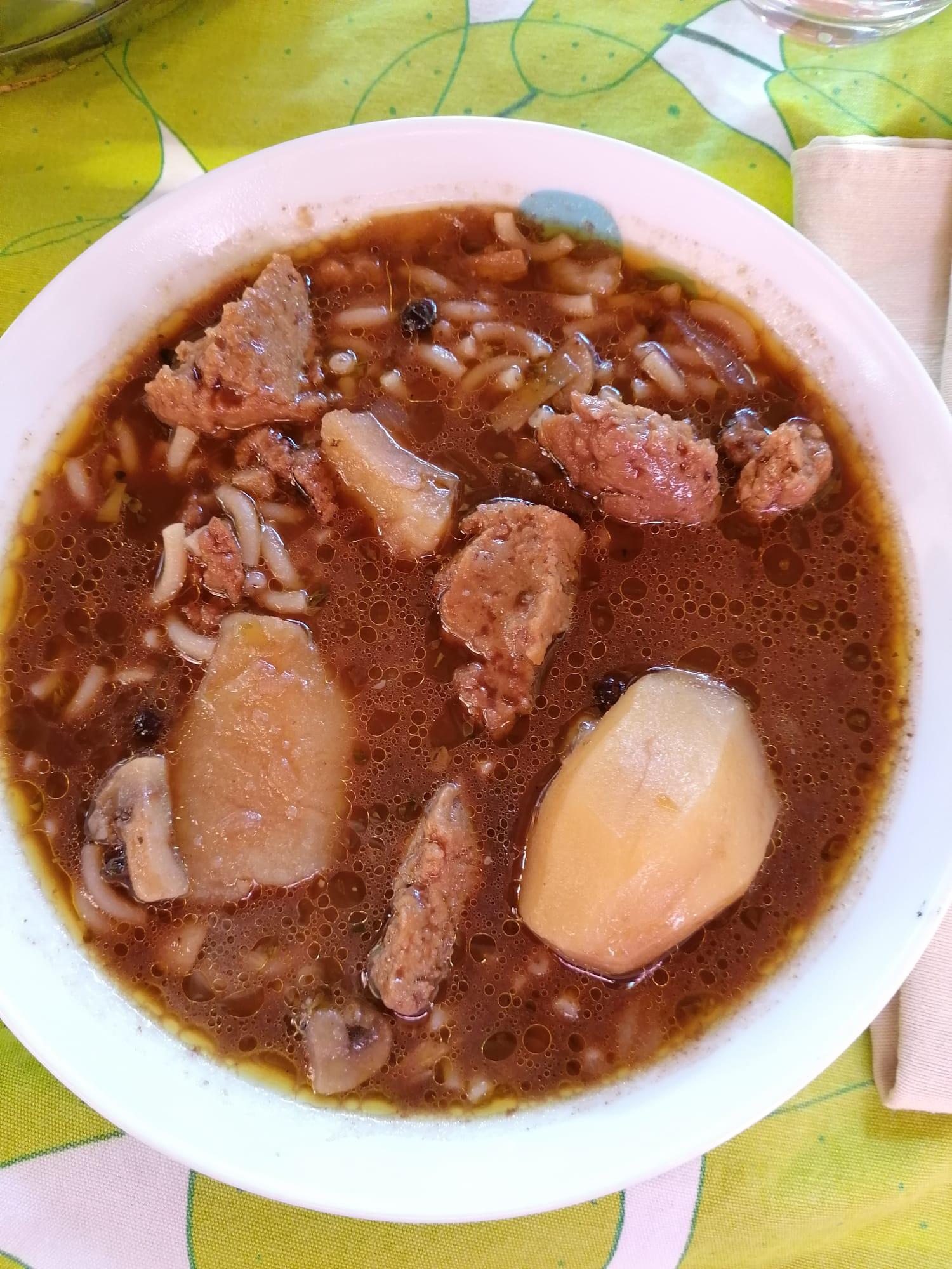 plano cenital del plato de guiso cartagenero veganizado con patatas enteras, seitán casero y pasta